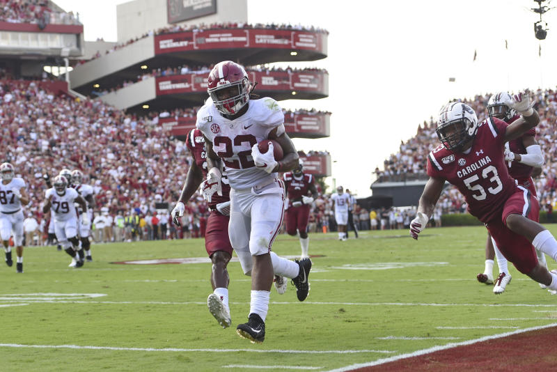 Alabama's Najee Harris, center, rushes past South Carolina's J.T. Ibe, left, and Ernest Jones for a touchdown during the first half of an NCAA college football game Saturday, Sept. 14, 2019, in Columbia, S.C. (AP Photo/Richard Shiro)