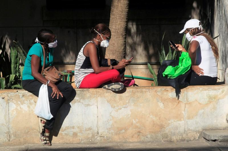 People use their mobile phones wearing protective masks amid concerns about the spread of the coronavirus disease (COVID-19) outbreak in Havana