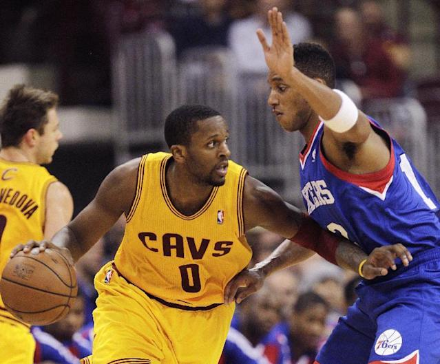 Cleveland Cavaliers' C.J. Miles, left, looks for an open pass as Philadelphia 76ers' Evan Turner defends during the second quarter of an NBA preseason basketball game Monday, Oct. 21, 2013, in Columbus, Ohio. (AP Photo/Jay LaPrete)