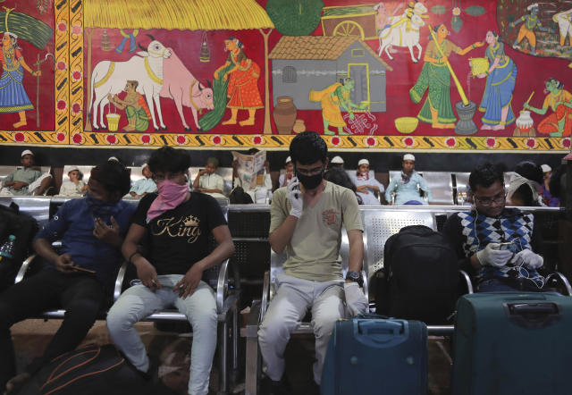 Indian passengers wear face masks and gloves as a precaution against COVID-19 wait at Secunderabad Railway Station in Hyderabad, India, Saturday, March 21, 2020. For most people, the new coronavirus causes only mild or moderate symptoms. For some it can cause more severe illness. (AP Photo/Mahesh Kumar A.)
