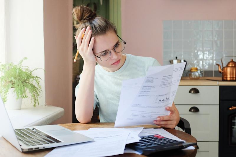 Young woman at laptop looks at documents