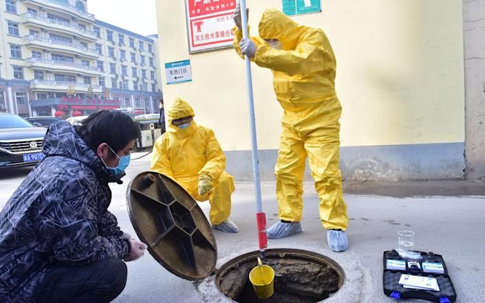 Workers of the ecology and environment bureau collect samples from the sewage system in Xinle, Hebei province, China - Reuters
