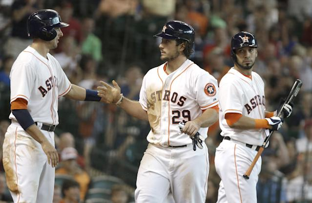Houston Astros' Brett Wallace (29) is welcomed home by Jason Castro, left, as Marwin Gonzalez looks on after scoring on a Brandon Barnes two-run double against the Toronto Blue Jays in the second inning of a baseball game Saturday, Aug. 24, 2013, in Houston. (AP Photo/Pat Sullivan)