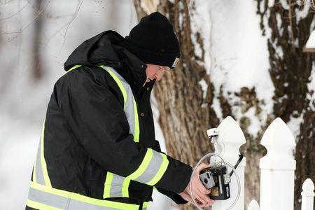 An Environmental Testing Associates employee checks an air monitor attached to the fence of a home in Boomer, West Virginia on Tuesday, February 17, 2015. REUTERS/Marcus Constantino