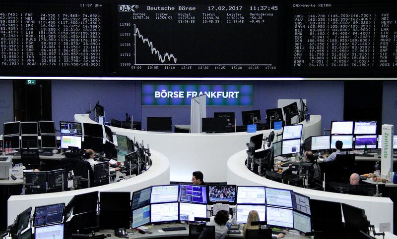 Traders work at their desks in front of the German share price index, DAX board, at the stock exchange in Frankfurt, Germany, February 17, 2017. REUTERS/staff/remote -
