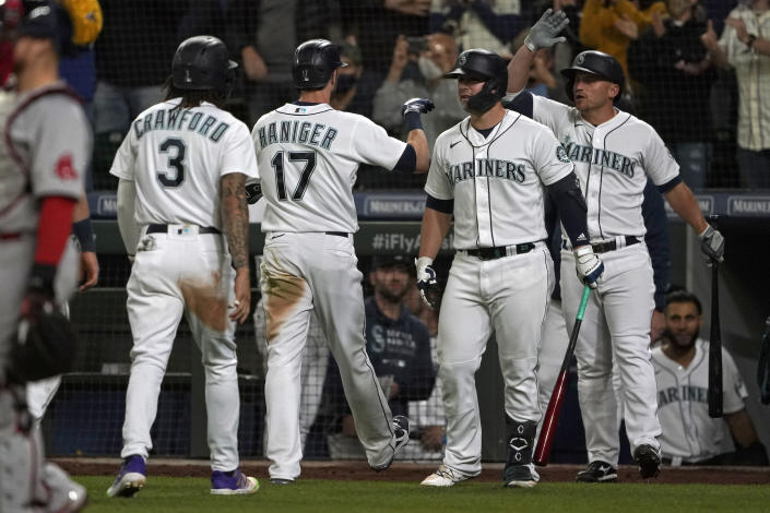Seattle Mariners' Mitch Haniger (17) is greeted by teammates after he hit a three-run go-ahead home run against the Boston Red Sox during the seventh inning of a baseball game, Monday, Sept. 13, 2021, in Seattle. (AP Photo/Ted S. Warren)