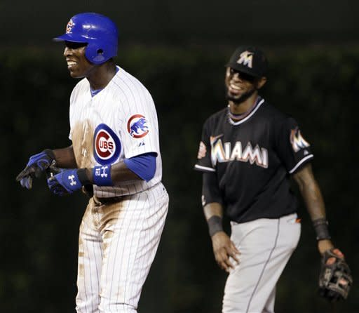 Chicago Cubs' Alfonso Soriano, left, smiles as he arrives at second base on a thrown wild pitch by Miami Marlins starter Josh Johnson during the seventh inning of a baseball game in Chicago, Wednesday, July 18, 2012. (AP Photo/Nam Y. Huh)