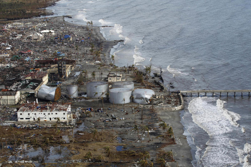 """FILE - This Nov. 13, 2013 file photo, shows typhoon damaged fuel tanks along the coast in Tanawan, central Philippines. A United Nations panel of scientists has drafted a list of eight ``key risks"""" about climate change that's easy to understand and illustrates the issues that have the greatest potential to cause harm to the planet. The list is part of a massive report on how global warming is affecting humans and the planet and how the future will be worse unless something is done about it. The report is being finalized at a meeting on the weekend of March 29, 2014 by the Intergovernmental Panel on Climate Change. (AP Photo/Wally Santana, File)"""