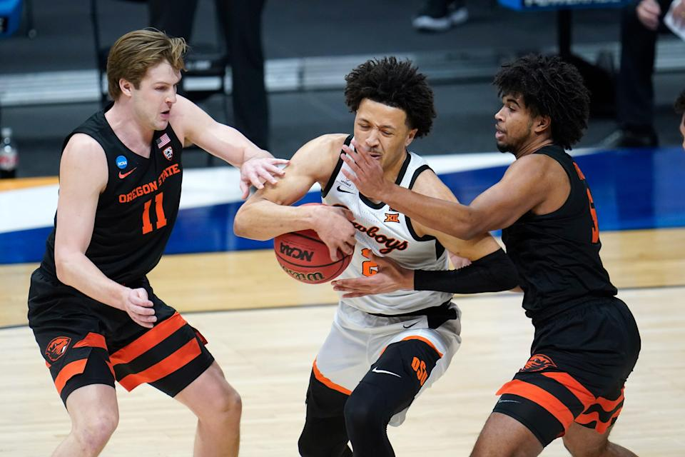 Oklahoma State guard Cade Cunningham (2) drives between Oregon State guard Zach Reichle (11) and Ethan Thompson (5) during the first half Sunday at Hinkle Fieldhouse in Indianapolis.
