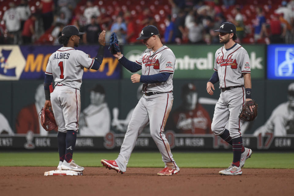 Atlanta Braves' Ozzie Albies, left, Adam Duvall, center, and Joc Pederson celebrate the teams's 6-1 victory over the St. Louis Cardinals in a baseball game Tuesday, Aug. 3, 2021, in St. Louis. (AP Photo/Joe Puetz)