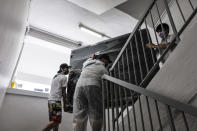 Volunteers of Keeping Hope Alive carry furniture up the stairs of a rental flat building Sunday, Oct. 4, 2020 in Singapore. Members of the volunteer group conduct weekend door-to-door visits to deliver goods or provide services to people in need. (AP Photo/Ee Ming Toh)