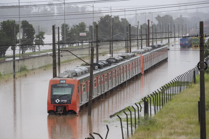 A metropolitan train is stuck at a flooded rail track running along the Pinheiros river in Sao Paulo, Brazil, Monday, Feb. 10, 2020. Heavy rains flooded the city, causing its main river to overflow its banks. (AP Photo/Andre Penner)