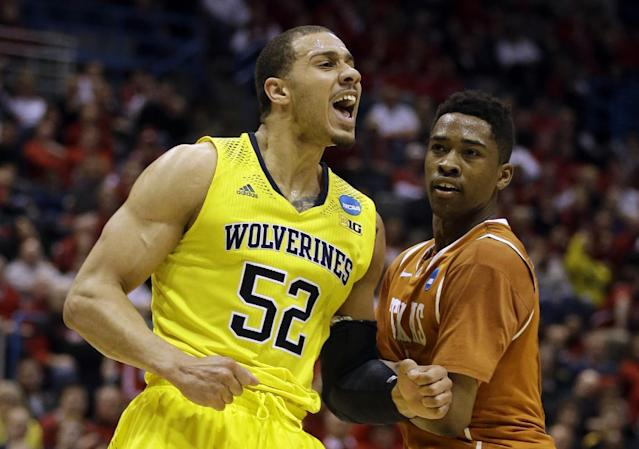 Michigan forward Jordan Morgan (52) reacts to a foul call as Texas guard Isaiah Taylor watches him during the second half of a third-round game of the NCAA college basketball tournament Saturday, March 22, 2014, in Milwaukee. (AP Photo/Jeffrey Phelps)