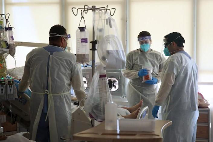 TORRENCE, CA - DECEMBER 29: Hospital doctors and nurses treat Covid-19 patients in a makeshift ICU wing on the West Oeste at Harbor UCLA Medical Center on Tuesday, Dec. 29, 2020 in Torrence, CA. The hospital has no open beds for incoming patients and have worked tirelessly to create additional beds for the influx of Covid-19 patients. (Dania Maxwell / Los Angeles Times)