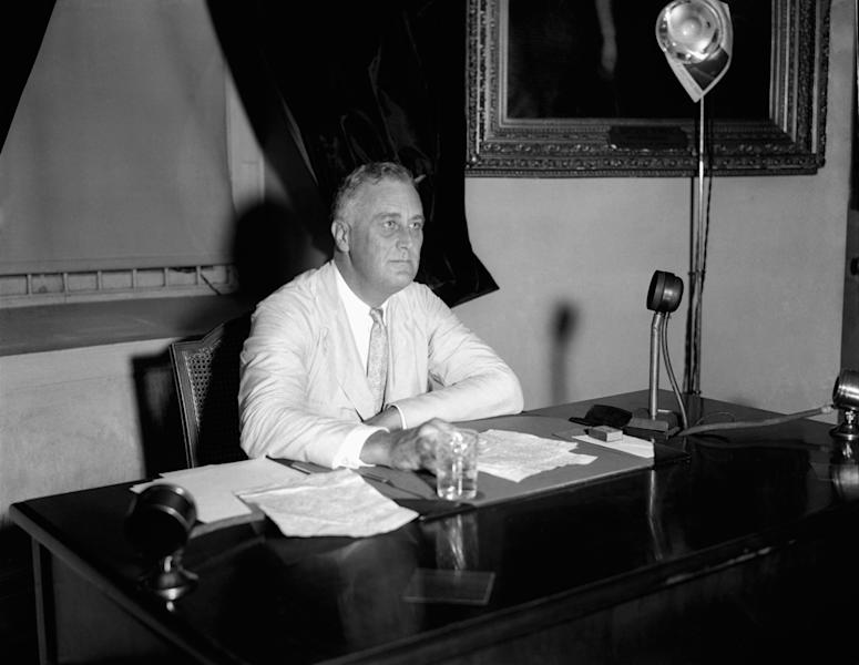 FILE - This July 24, 1933 file photo shows President Franklin D. Roosevelt appealing to the nation via radio for immediate enrollment of all employers under the blanket agreement to raise wages and create jobs, in Washington. When the Senate debates a Democratic proposal to raise the federal minimum wage, some workers won't benefit even if lightning strikes and the long-shot effort prevails. When Roosevelt signed the bill into law, the minimum wage was set at 25 cents an hour, mainly covering industrial jobs related to interstate commerce. To win crucial votes from Southern Democrats in Congress, Roosevelt agreed to exclude occupations including agriculture laborers and domestic workers, who were largely black. (AP Photo, File)