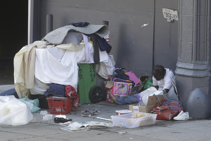 A homeless person sits on the street in San Francisco, Thursday, April 2, 2020. Since the beginning of an international pandemic, officials in California have said one population is particularly vulnerable to contracting the coronavirus and spreading it to others: the homeless. (AP Photo/Jeff Chiu)