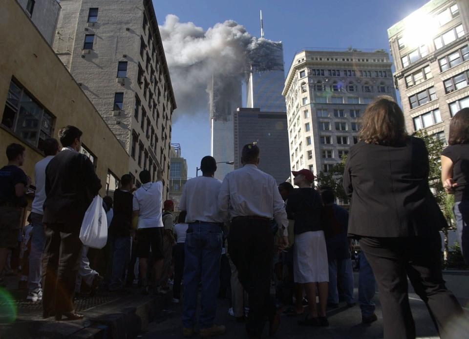 FILE - In this Tuesday, Sept. 11, 2001 file photo, pedestrians in lower Manhattan watch smoke rise from the World Trade Tower after an early morning terrorist attack on the New York landmark. The terrorist attacks that day shattered Americans' sense of security and ushered in a new era of nebulous threats, hidden enemies and a seemingly never-ending war on terror. And for then-Sen. Joe Biden they marked a new phase of his public life. (AP Photo/Amy Sancetta, File)