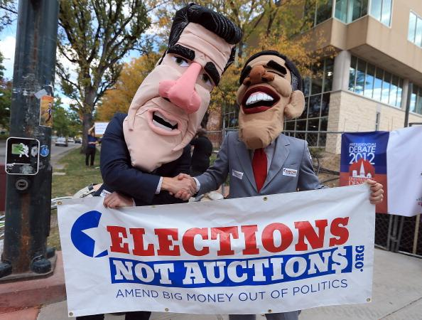 DENVER, CO - OCTOBER 03:  Demonstrators costumed as Republican presidential nominee, former Massachusetts Gov. Mitt Romney and U.S. President Barack Obama bring attention to campaign finance reform prior to the Presidential Debate at the University of Denver on October 3, 2012 in Denver, Colorado. The first of four debates for the 2012 Election, three Presidential and one Vice Presidential, is moderated by PBS's Jim Lehrer and focuses on domestic issues: the economy, health care, and the role of government.  (Photo by Doug Pensinger/Getty Images)