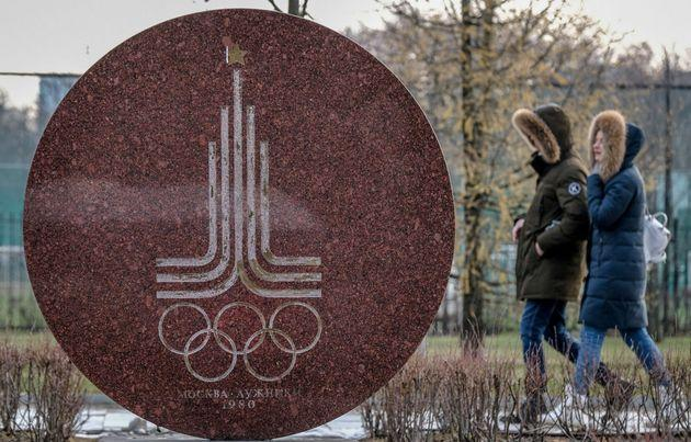 A couple walks behind a monument featuring the emblem of the 1980 Moscow Olympics near the Luzhniki stadium in Moscow on December 6, 2019. - The executive committee of the World Anti-Doping Agency will meet in Lausanne on December 9 to consider a recommendation for the ban, which would exclude Russians from major sports events including the 2020 Tokyo Olympics and 2022 Beijing Winter Olympics. A WADA review panel has accused Moscow of falsifying laboratory data handed over to investigators as part of a probe into the doping allegations that have plagued Russia for years. (Photo by Yuri KADOBNOV / AFP) (Photo by YURI KADOBNOV/AFP via Getty Images)