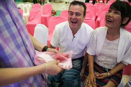 Public health officer gives a prenatal vitamins to a couple during a Valentine's Day celebration at the Laksi district in Bangkok, Thailand February 14, 2018. REUTERS/Athit Perawongmetha