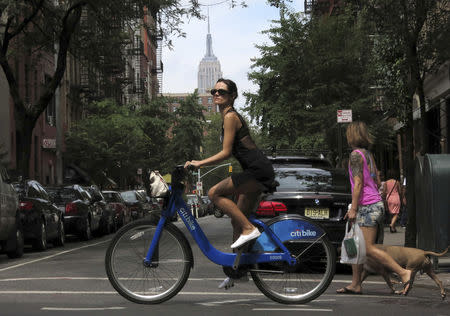 FILE PHOTO: The Empire State Building is seen in the distance as a woman rides a Citibike in the Soho neighbourhood of New York July 27, 2013. REUTERS/Gary Hershorn/File Photo