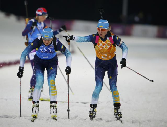 Ukraine's Valj Semerenko hands over to her team mate Olena Pidhrushna (L) during the women's biathlon 4x6 km relay event at the Sochi 2014 Winter Olympic Games February 21, 2014. REUTERS/Carlos Barria (RUSSIA - Tags: OLYMPICS SPORT BIATHLON)