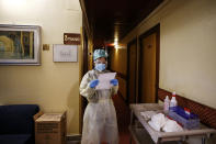 Medical staff of the Gemelli hospital checks a list as she tours the rooms of the Pineta Palace Hotel where patients recovering from COVID-19 are undergoing quarantine under the supervision of the Gemelli hospital, in Rome, Saturday, Nov. 14, 2020. (Cecilia Fabiano/LaPresse via AP)