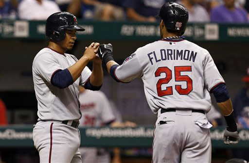 Minnesota Twins' Eduardo Escobar, left, congratulates teammate Pedro Florimon who hit them both in with a two-run home run during the third inning of a baseball game against the Tampa Bay Rays, Wednesday, July 10, 2013, in St. Petersburg, Fla. (AP Photo/Mike Carlson)