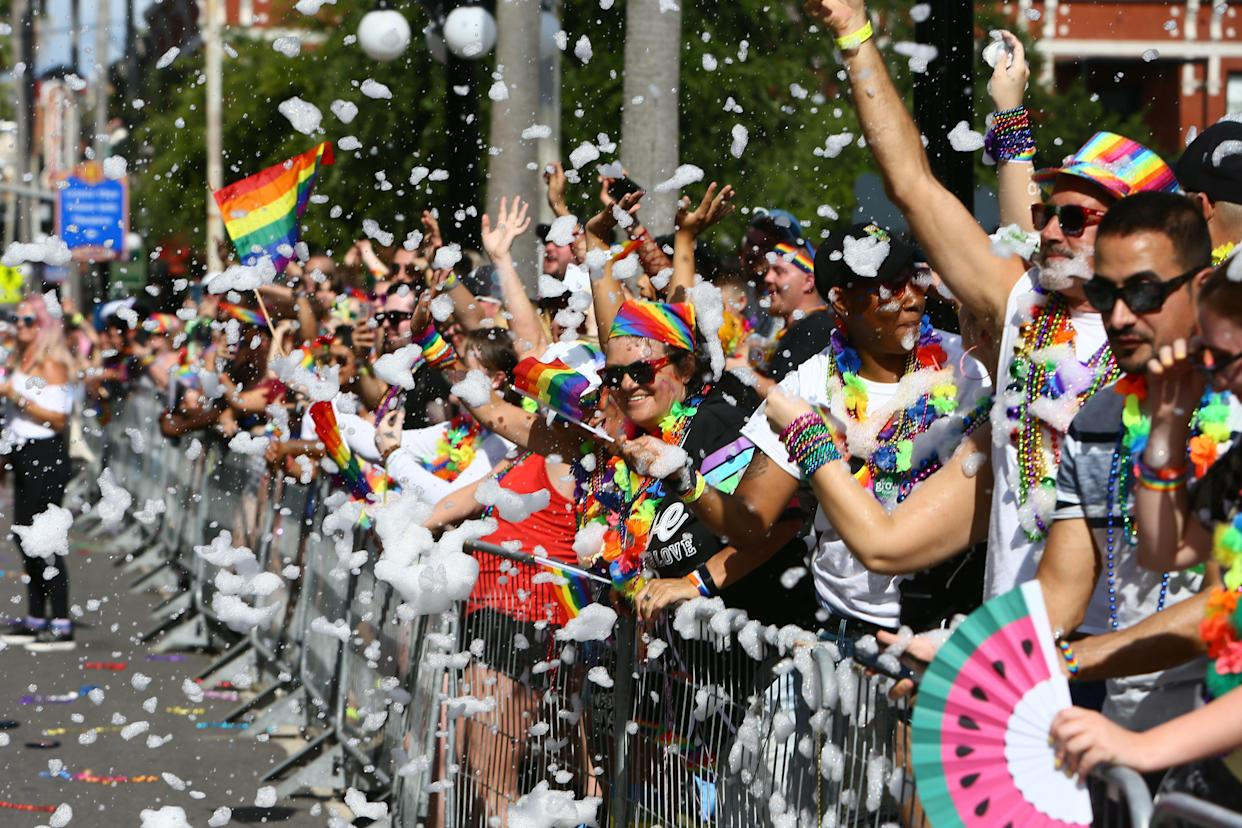 Smiling faces and bright colors are seen behind a wall of bubbles and foam being sprayed to the crowd during the Tampa Pride Diversity Parade, on Saturday, May 22, 2021 in Ybor City, Florida. (Luis Santana/Tampa Bay Times via ZUMA Wire)