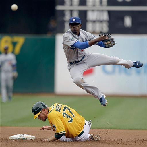 Los Angeles Dodgers shortstop Dee Gordon hops over Oakland Athletics' Brandon Moss (37) as he completes a double play throw to first base during the second inning of a baseball game Thursday, June 21, 2012, in Oakland, Calif. The A's Derek Norris was out at first base on the play. (AP Photo/Ben Margot)
