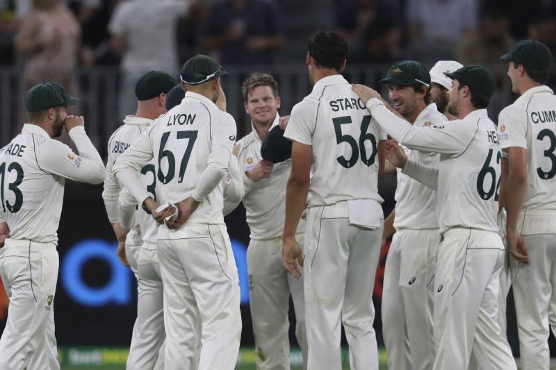 Australia's Steve Smith, center without cap, is congratulated by teammates after taking the catch to dismiss New Zealand's Kane Williamson during their cricket test match in Perth, Australia, Friday, Dec. 13, 2019. (AP Photo/Trevor Collens)