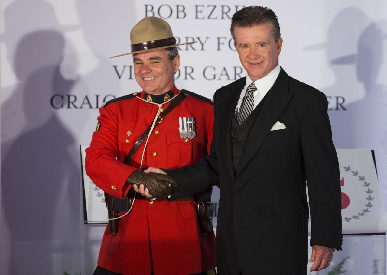 Actor and honouree Alan Thicke shakes hands with a Royal Canadian Mounted Police officer during Canada's Walk of Fame induction ceremonies in Toronto, September 21, 2013. REUTERS/Mark Blinch (CANADA - Tags: ENTERTAINMENT)