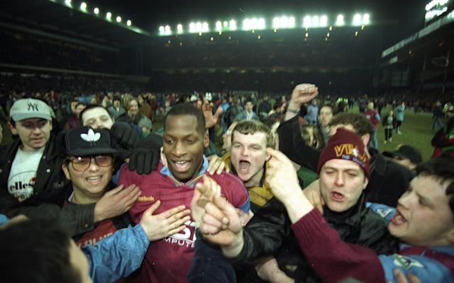 <span>Ugo Ehiogu of Aston Villa is surrounded by fans after the Coca Cola Cup semi-final against Arsenal in 1996</span> <span>Credit: Getty Images </span>