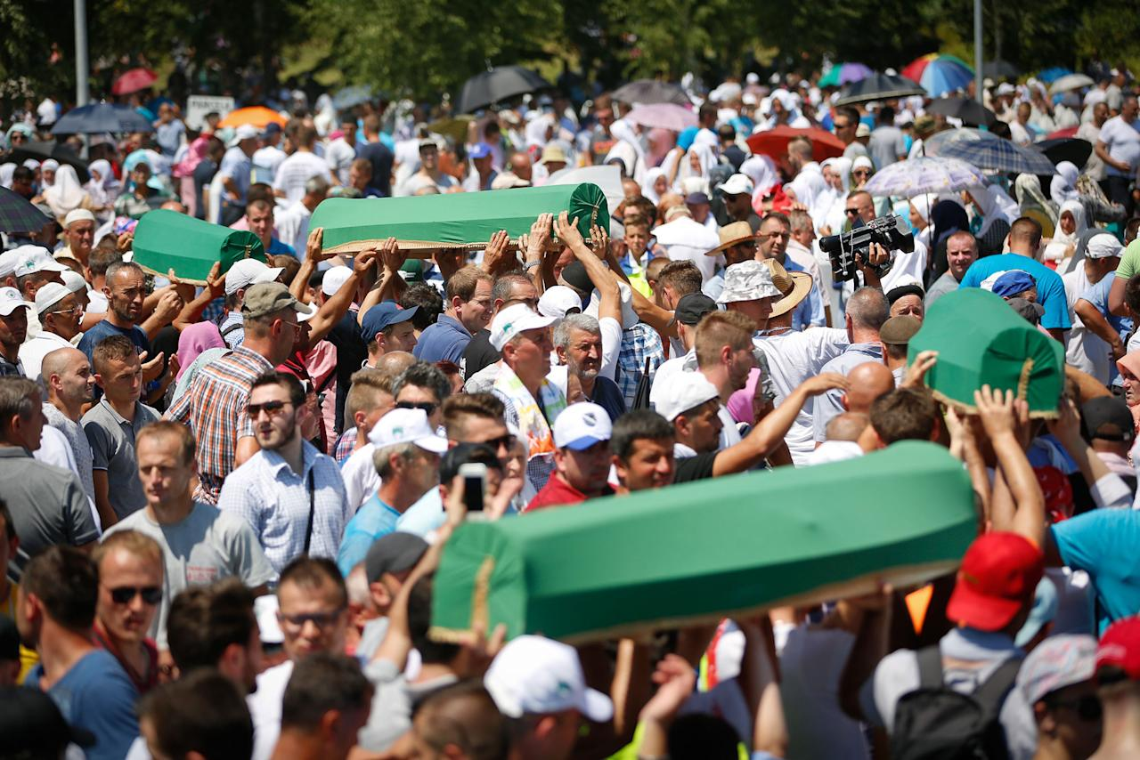 <p>People carry the coffin during a funeral ceremony of newly identified 71 Srebrenica genocide victims, to mark the 22nd anniversary of the Srebrenica genocide, at Potocari Memorial Center in Potocari village of Srebrenica, Bosnia and Herzegovina on July 11, 2017. (Photo: Mustafa Ozturk/Anadolu Agency/Getty Images) </p>