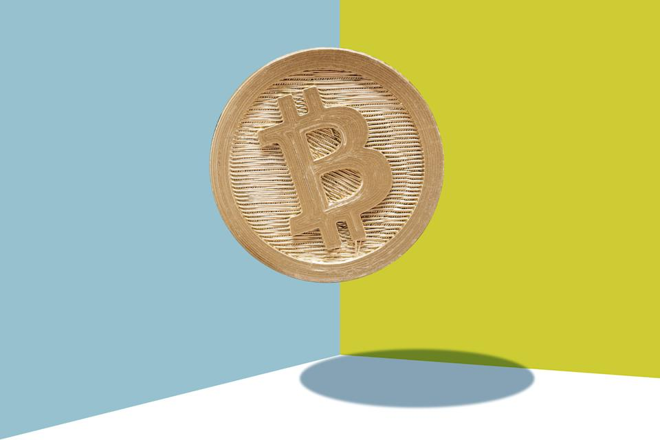 Gold Bitcoin Suspended on a blue and yellow background.