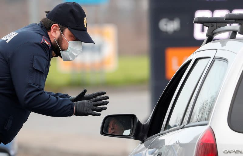 FILE PHOTO: A policeman wearing a face mask warns a driver on the road between Codogno and Casalpusterlengo, which has been closed by the Italian government due to a coronavirus outbreak in northern Italy