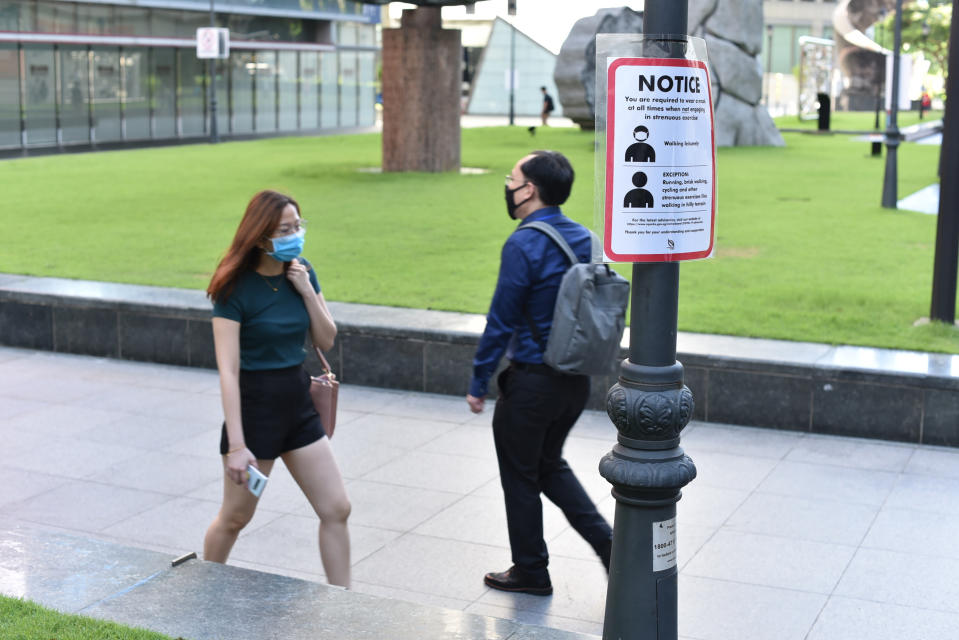 A notice reminding people to wear masks hangs on a post as people walk by in Singapore on 2 June, 2020. (PHOTO: AP)