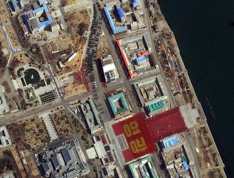 "FILE - This April 15, 2012 satellite image provided by DigitalGlobe shows a parade held to mark the 100th anniversary of Kim Il Sung's birthday Pyongyang, North Korea. The parade can be seen from the top center of the frame as it makes it way toward Kim Il Sung Square in the lower right hand corner where a large formation of people in red and gold clothing spell out the word ""glory""  in Korean.  The parade culminated with the unveiling of a new long-range missile, though it's not clear how powerful or significant the addition to the North Korean arsenal is. Some analysts suggested it might have been a dummy designed to dupe outside observers. (AP Photo/DigitalGlobe, File)"