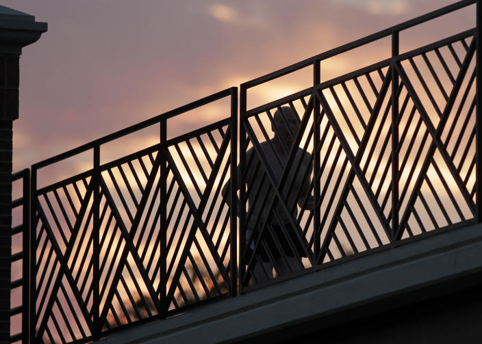 A runner makes his way across a bridge on the Monon Trail in Carmel, Ind., as the sun rises Thursday, June 28, 2012. Temperatures are expected to reach 100 degree in Central Indiana later in the day. (AP Photo/Michael Conroy)