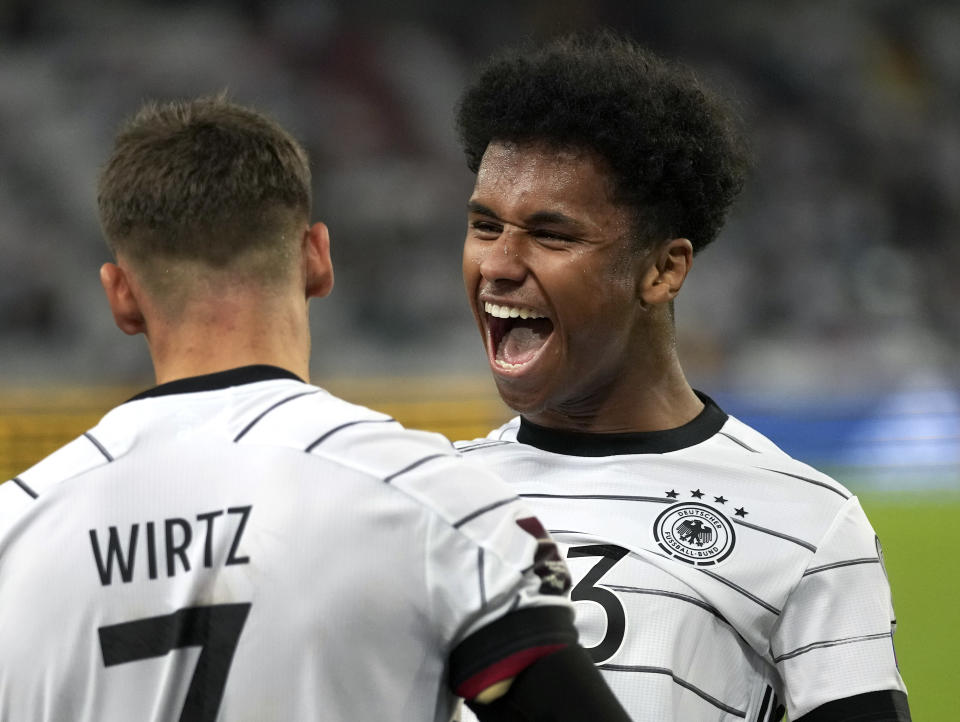 Germany's scorer Karim Adeyemi, right, and his teammate Florian Wirtz celebrate their side's sixth goal during the World Cup 2022 group J qualifying soccer match between Germany and Armenia at Mercedes-Benz Arena stadium in Stuttgart, Germany, Sunday, Sept. 5, 2021. (AP Photo/Matthias Schrader)