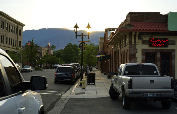 """In this June 30, 2021 photo, the sun sets at the front of the town of Minden, Nev. Efforts to silence the century-old siren that blares every night at 6 p.m. are sparking debates over how to confront the region's history of racism and violence. The Washoe Tribe of Nevada and California associates the siren with a historic """"sundown ordinance"""" that once made it illegal for them to be in Minden and neighboring Gardnerville after nightfall. Residents of the mostly white town defend it as a tradition that marks time and honors first responders. (AP Photo/Sam Metz)"""