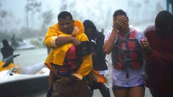 PHOTO: A family is escorted to a safe zone after they were rescued as Hurricane Dorian continues to rain in Freeport, Bahamas, Sept. 3, 2019. (Ramon Espinosa/AP)
