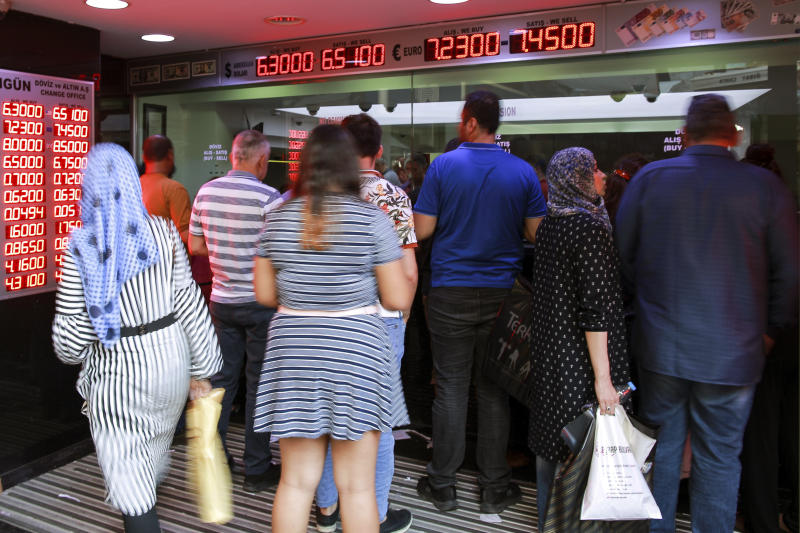People queue outside a currency exchange shop in an Istanbul's market, Friday, Aug. 10, 2018. A financial shockwave ripped through Turkey on Friday as its currency nosedived on concerns about its economic policies and a dispute with the U.S., which President Donald Trump stoked further with a promise to double tariffs on the NATO ally. (AP Photo/Mucahid Yapici)