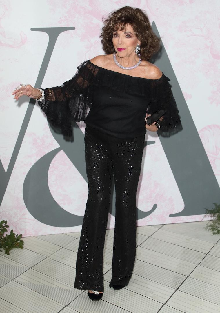 Not one to shy away from sequins, Dame Joan Collins chose a sparkly cold-shoulder jumpsuit for the outing. <em>[Photo: Getty]</em>