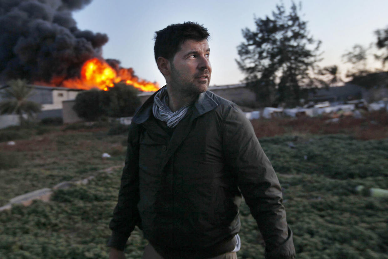Chris Hondros in front of a burning building while on assignment on April 18, 2011, in Misrata, Libya. (Photo: Katie Orlinsky via Getty Images)