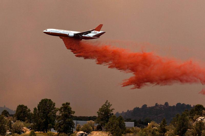 Tanker 910 makes a retardant drop Yarnell Hill Fire to help protect the Double Bar A Ranch near Peeples Valley, Ariz., Sunday, June 30, 2013. The fire started Friday and picked up momentum as the area experienced high temperatures, low humidity and windy conditions. It has forced the evacuation of residents in the Peeples Valley area and in the town of Yarnell. (AP Photo/The Arizona Republic, Tom Story)