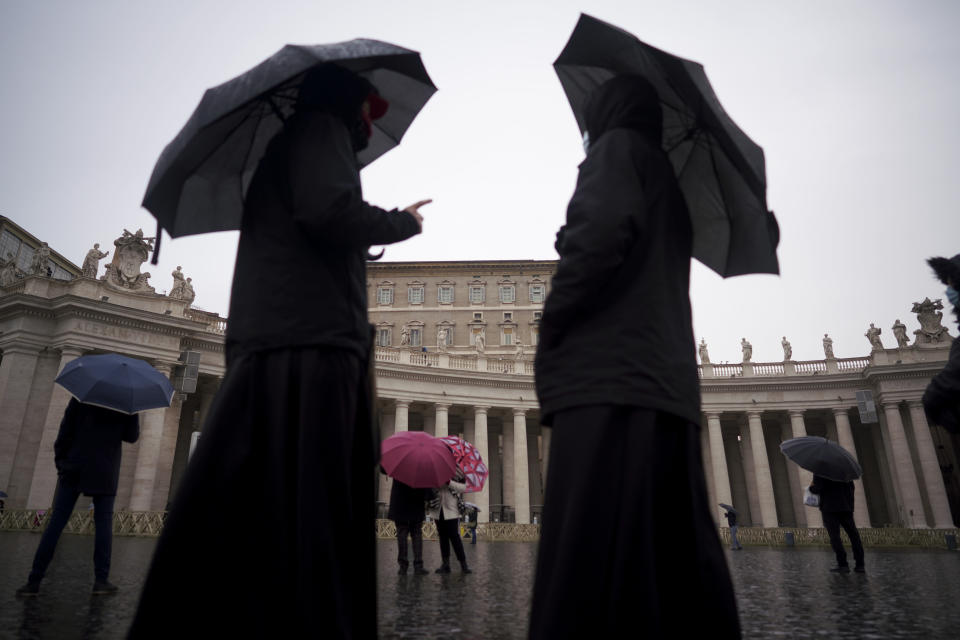 "Priests walk in an empty St. Peter's Square in front of the Apostolic Palace where Pope Francis is reciting the Angelus noon prayer in his studio, at the Vatican, Sunday, Jan. 17, 2021. ""I pray for the dead, for the injured and for who lost their home or work,'' Francis said following the weekly Angelus blessing, delivered from the Apostolic Palace library and not from his usual perch, a window overlooking St. Peter's Square, due to COVID-19 restrictions. (AP Photo/Andrew Medichini)"