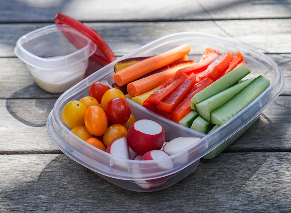 pre cut veggies carrots peppers cucumbers radishes tomatoes in meal prep container for easy snacking
