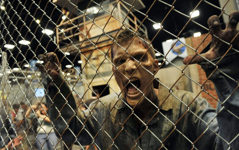 "A zombie character in an exhibit inspired by the television series ""The Walking Dead"" screams at onlookers during the Preview Night event on Day 1 of the 2013 Comic-Con International Convention on Wednesday, July 17, 2013 in San Diego, Calif. (Photo by Chris Pizzello/Invision/AP)"