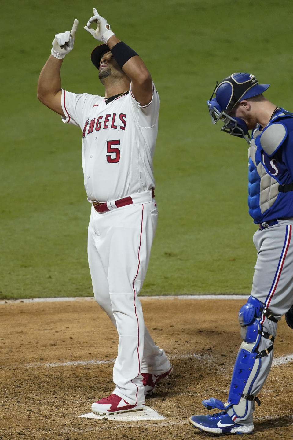 Los Angeles Angels' Albert Pujols points skyward he crosses home plate after a solo home run, next to Texas Rangers Sam Huff during the fifth inning of a baseball game Friday, Sept. 18, 2020, in Anaheim, Calif. (AP Photo/Ashley Landis)
